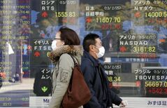 People walk by an electronic stock board of a securities firm in Tokyo, Monday, Feb. 25, 2013. Japanese stocks led Asian markets higher Monday, jumping on a report that the prime minister's pick for the next central bank governor will be a strong advocate of loose monetary policy aimed at reviving the moribund economy. (AP Photo/Koji Sasahara)