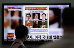 A woman watches a TV news program on the reward poster of Yoo Byung-eun at the Seoul Train Station in Seoul, South Korea, Monday, May 26, 2014. South Korea has boosted to half a million dollars a reward for tips about the mysterious billionaire who prosecutors say owns a ferry that sank last month, police said Monday. (AP Photo/Lee Jin-man)