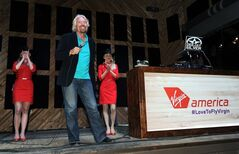 In this Monday, May 5, 2014 photo released by Virgin America Airlines, Virgin Group Founder Sir Richard Branson is joined by Virgin America teammates during an informal