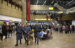 In this June 5, 2014 photo, policemen patrol at the Guarulhos International Airport, in Sao Paulo, Brazil. Only a quarter of the new $1.3 billion international terminal is operational. Many weary travelers will deplane into a poorly-lit terminal with severe concrete architecture dating from the military dictatorship of three decades ago. (AP Photo/Andre Penner)