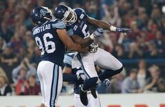 Toronto Argonauts linebacker Ejiro Kuale (right) and teammate defensive tackle Armond Armstead celebrate a tackle during second quarter CFL Grey Cup action against the Calgary Stampeders in Toronto on Sunday, November 25, 2012. THE CANADIAN PRESS/Sean Kilpatrick