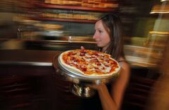 Manager Cynthia Murray floats by with a Crudo pizza.