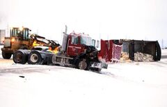 A gravel semi-truck lies at the side of the road after a collision with a pickup truck on the Perimeter Highway.