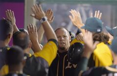 Oakland Athletics' Brandon Moss, center, is congratulated by teammates after scoring against the Los Angeles Angels during the fifth inning of a baseball game, Thursday, Aug. 28, 2014, in Anaheim, Calif. (AP Photo/Mark J. Terrill)