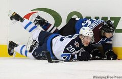 Winnipeg Jet Antti Miettinen, left, and Colorado Avalanche centre Jay McClement, fall down against the boards in the first period of an NHL hockey game Tuesday in Denver.