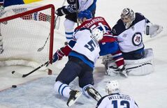The Montreal Canadiens score past Winnipeg Jets goalie Ondrej Pavelec and defenceman Mark Stuart on Sunday in Montreal.