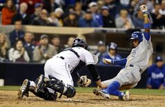 San Diego Padres catcher Yasmani Grandal dives to make a tag on Kansas City Royals' Alcides Escobar, right, who was out trying to score from third on a pop out down the right field line during the ninth inning of a tied baseball game Tuesday, May 6, 2014, in San Diego. (AP Photo/Lenny Ignelzi)