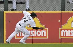 Chicago White Sox left fielder Dayan Viciedo chases down a double by Cleveland Indians' Carlos Santana during the first inning of a baseball game in Chicago, Tuesday, Aug. 26, 2014. (AP Photo/Paul Beaty)