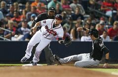 Miami Marlins' Christian Yelich (21) steals third base as Atlanta Braves third baseman Chris Johnson (23) handles the late throw in the eighth inning of baseball game in Atlanta, Wednesday, July 23, 2014. (AP Photo)