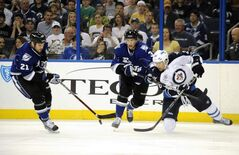 Tampa Bay Lightning right winger Brandon Segal, left, and defenceman Keith Aulie, centre, battle for the puck against Winnipeg Jets right winger Blake Wheeler in Tampa, Fla., Saturday.