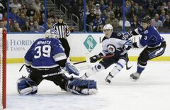 Tampa Bay Lightning goalie, Anders Lindback, kicks away a shot by Winnipeg Jets centre Mark Scheifele during the first period in Tampa, Fla. The Jets lost 8-3.