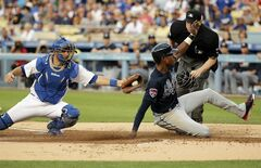 Atlanta Braves' B.J. Upton, right, scores on a sacrifice fly hit by Justin Upton as Los Angeles Dodgers catcher Drew Butera applies a late tag during the first inning of a baseball game on Tuesday, July 29, 2014, in Los Angeles. (AP Photo/Jae C. Hong)