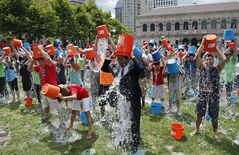 Boston City Councillor Tito Jackson, center in suit, leads some 200 people in the ice bucket challenge at Boston's Copley Square, Thursday, Aug. 7, 2014 to raise funds and awareness for ALS. The idea is easy: Take a bucket of ice water, dump it over your head, video it and post it on social media. Then challenge your friends, strangers, even celebrities to do the same within 24 hours or pay up for charity. (AP Photo/Elise Amendola)