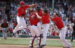 Boston Red Sox's Jonathan Herrera, center, celebrates his game-winning RBI single with teammates Xander Bogaerts, left, David Ross (3), Koji Uehara, second from right, and Mike Napoli, right, in the ninth inning of the first game of a baseball doubleheader against the Baltimore Orioles in Boston, Saturday, July 5, 2014. The Red Sox won 3-2. (AP Photo/Michael Dwyer)