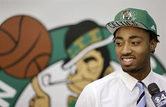 Boston Celtics 2014 NBA basketball draft pick James Young stands in front of a Boston Celtics logo while speaking with members of the media, Monday, June 30, 2014, in Waltham, Mass. (AP Photo/Steven Senne)
