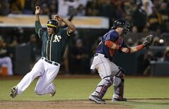 Oakland Athletics' Kyle Blanks, left, slides to score behind Boston Red Sox catcher A.J. Pierzynski in the eighth inning of a baseball game Friday, June 20, 2014, in Oakland, Calif. Blanks scored on a single by Coco Crisp. (AP Photo/Ben Margot)