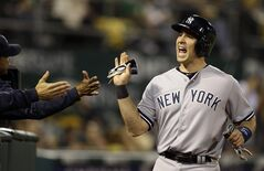 New York Yankees' Mark Teixeira is congratulated after scoring against the Oakland Athletics in the eighth inning of a baseball game Friday, June 13, 2014, in Oakland, Calif. Teixeira scored on a hit by Ichiro Suzuki. (AP Photo/Ben Margot)