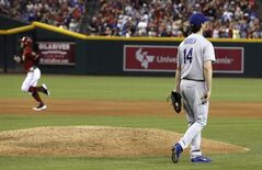 Los Angeles Dodgers' Dan Haren (14) walks around the pitcher's mound with a new baseball after giving up a home run to Arizona Diamondbacks' Cody Ross, left, during the fourth inning of a baseball game on Sunday, May 18, 2014, in Phoenix. (AP Photo/Ross D. Franklin)