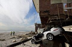 A badly damaged home is entangled with a vehicle along the beach in the Belle Harbor section of the borough of Queens, N.Y., in the wake of Superstorm Sandy.
