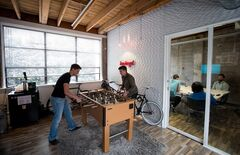 Hubert Florin, left, a senior designer, and Ryan Betts, direct of user experience, play foosball during a break as others hold a meeting at Bazinga! in Vancouver, B.C., on Wednesday August 13, 2014. The company offers a cloud-based platform for online interaction between residents in condo buildings and property management and developers. THE CANADIAN PRESS/Darryl Dyck