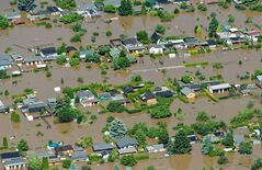 FILE - In this June 5, 2013 aerial view file picture , houses stand in the floods of Elbe river in Riesa, eastern Germany. A leading insurance company says flooding in central Europe last month caused damage totaling more than US $16 billion, about a quarter of it insured — making it the year's costliest natural disaster so far. Munich Re AG put insured losses from the flooding in Germany and several other countries at US $3.9 billion. Both figures were similar to the damage caused by floods in 2002 that hit some of the same areas. Munich Re said Tuesday July 9, 2013 that overall losses caused by natural disasters totaled a below-average US $45 billion between January and June, with insured losses totaling US $13 billion. May's deadly tornadoes in Oklahoma were the second-costliest disaster in the period, causing overall losses of US $3.1 billion — nearly US $1.6 billion of that covered by insurance. (AP Photo/dpa,Patrick Pleul,ile)