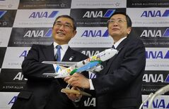 All Nippon Airways' Chief Executive Officer and President Shinichiro Ito, left, and Vice President Osamu Shinobe hold a desk-top model of Boeing 767 during a press conference at the company's office in Tokyo Friday, March 1, 2013. The president of ANA, Boeing's biggest single customer for its troubled 787 Dreamliner, said Friday that he believes the U.S. manufacturer has made progress in resolving problems with the aircraft's lithium-ion batteries. (AP Photo/Junji Kurokawa)