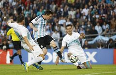 Argentina's Lionel Messi, center, scores past Slovenia's Miral Samardzic, right, and Bojan Jokic during their international friendly soccer match in La Plata, Argentina, Saturday, June 7, 2014. Argentina's team is leaving June 9 for Brazil to compete in the World Cup. (AP Photo/Natacha Pisarenko)