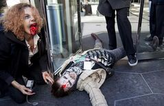 A member of the Occupy Vancouver movement lays on on the ground at the front doors of the Embridge offices during a Zombie Walk through downtown Vancouver, B.C. Monday, Oct. 31, 2011. If zombies do eventually strike in Quebec, the province's public security department wants to be ready.Participants at an annual symposium on civil security next week will be discussing how to handle a zombie attack in the province, among other topics.THE CANADIAN PRESS/Jonathan Hayward