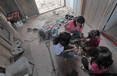 Kids play in a Garden Hill porch near a slop pail used as a toilet.