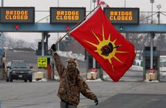 A man waves a flags as aboriginal protesters and supporters in the Idle No More movement block the Blue Water Bridge border crossing to the United States in Sarnia, Ont. on Saturday, January 5, 2013.THE CANADIAN PRESS/Dave Chidley