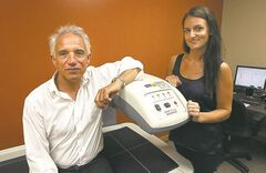 Peter Jones and Jaclyn Omar with a dual energy X-ray absorptiometry scanner.
