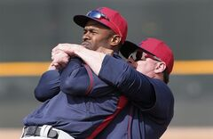 Cleveland Indians' Jason Giambi, right, cracks Michael Bourn's back during spring training baseball practice in Goodyear, Ariz., Friday, Feb. 21, 2014. (AP Photo/Paul Sancya)