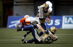 B.C. Lions' Dante Marsh, left, collides with Winnipeg Blue Bombers' Rory Kohlert, bottom, as Nick Moore, back, carries the ball during the first half of a CFL football game in Vancouver, B.C., on Friday July 25, 2014.