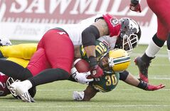 Calgary Stampeders Jock Sanders (2) tackles Edmonton Eskimos John White (30) during first half action in Edmonton on July 24, 2014. The Battle of Alberta will also be for top spot in the CFL's standings. The Calgary Stampeders host the Edmonton Eskimos on Monday to kick off their annual Labour Day home-and-home series. THE CANADIAN PRESS/Jason Franson