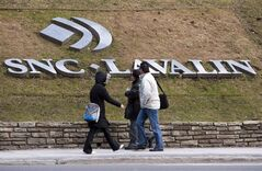 Pedestrians walk past the offices of SNC Lavalin, in Montreal, March 26, 2012. Canada's largest engineering company has admitted to participating in illegal political financing in Quebec. THE CANADIAN PRESS/Ryan Remiorz