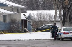 A policeman stands watch outside the house that was the scene of a multiple fatal stabbing incident in Calgary on April 16, 2014. THE CANADIAN PRESS/Larry MacDougal
