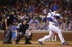 Chicago Cubs first baseman Anthony Rizzo, right, watches his seventh inning home run as San Diego Padres catcher Yasmani Grandal, center, and umpire Pat Hoberg (31) look on during a baseball game in Chicago, Tuesday, July 22, 2014. This was Rizzo's second home run of the game. (AP Photo/Jeff Haynes)