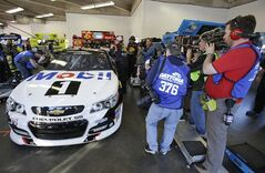 Photographers surround driver Tony Stewart's car as he gets ready to go out on the track to practice for the Sprint Unlimited auto race at Daytona International Speedway in Daytona Beach, Fla., Friday, Feb. 14, 2014. Stewart has not raced in more than six months since he broke two bones in his leg in an August sprint-car crash. (AP Photo/John Raoux)