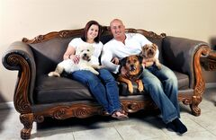 In this July 2014 photo provided by Kris Rotonda, Rotonda, who founded YouMustLoveDogsDating.com, poses with his girlfriend Denise Fernandez and three of his four dogs, Kobe, a bichon frise, Jordan, a bull mastiff German shepherd and Samoyed mix, and Coco, a Yorkie in Clearwater, Fla.