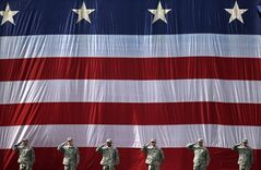 Soldiers stand at attention for the national anthem before a baseball game between the Boston Red Sox and the Cleveland Indians in Boston, Saturday, June 14, 2014. (AP Photo/Michael Dwyer)