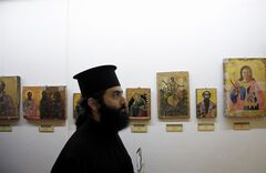 A Christian Orthodox priest looks at returned looted icons at the Byzantine Museum in capital Nicosia, Cyprus, Tuesday, Nov. 12, 2013. The largest haul of looted church icons, frescoes and mosaics ever repatriated to Cyprus has been officially welcomed after a nearly four-decade journey. A ceremony marked the return of 173 items stolen from Orthodox and Maronite Christian churches in the Turkish Cypriot northern part Cyprus. The island was ethnically split in 1974 when Turkey invaded after a coup by supporters of union with Greece. (AP Photo/Petros Karadjias)
