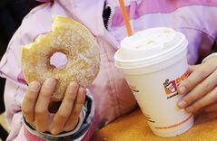 "FILE - In this Feb. 14 2014 file photo, a girl holds a doughnut and a beverage at a Dunkin' Donuts in New York. Dunkin' Brands CEO Nigel Travis said in a phone interview Thursday, July 24, 2014, that the company is pushing to get its cashiers to ""upsell"" to afternoon customers. It's part of an effort to increase sales after stores have emptied out after the morning rush. (AP Photo/Mark Lennihan, File)"