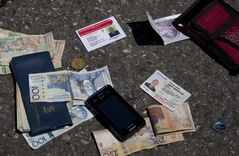 Identification cards, cash, a phone, a key and an item with a bank logo lay on the street after being placed there by authorities next to the body of Canadian priest Richard E. Joyal, not in picture, after he was killed in Delmas, a district of Port-au-Prince, Haiti, Thursday, April 25, 2013. Police inspector Aladin Jean-Louis says that the 62-year-old Joyal had just withdrawn $1,000 from a bank when two men on a motorcycle approached and grabbed a bag he was carrying, and the passenger shot him three times in the back. Authorities later found the $1,000 in Joyal's wallet in his pocket and placed it at his feet. (AP Photo/Dieu Nalio Chery)