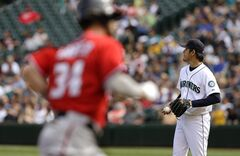 Seattle Mariners starting pitcher Hisashi Iwakuma, right, stands on the mound Washington Nationals' Bryce Harper, left, rounds the bases in the fourth inning after Harper hit his second solo home run off him in a baseball game on Sunday, Aug. 31, 2014, in Seattle. (AP Photo/Ted S. Warren)