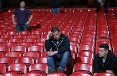 A Liverpool supporter sits in the stand following the end of the English Premier League soccer match between Crystal Palace and Liverpool at Selhurst Park stadium in London, Monday, May 5, 2014. The game ended in a 3-3 draw. (AP Photo/Alastair Grant)