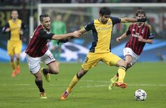 Atletico Madrid's Brazilian forward Diego Costa, right, challenges for the ball with AC Milan defender Adil Rami, of France, during a round of 16th Champions League soccer match between AC Milan and Atletico Madrid at the San Siro stadium in Milan, Italy, Wednesday, Feb. 19, 2014. (AP Photo/Emilio Andreoli)