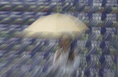 A woman with an umbrella stands in front of an electronic stock indicator of a securities firm in Tokyo, Friday, June 6, 2014. Asian stocks were mostly indifferent on Friday to the unveiling of a big stimulus package from the European Central Bank as investors awaited the U.S. jobs report for May. (AP Photo/Eugene Hoshiko)