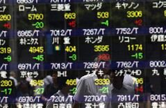 Pedestrians are reflected on an electronic stock board of a securities firm in Tokyo, Wednesday, July 9, 2014. Asian stock markets fell for a third day Wednesday as caution spread ahead of corporate earnings and after record highs on Wall Street. (AP Photo/Eugene Hoshiko)