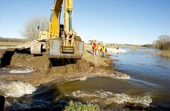 A backhoe makes the cut in the dike at Hoop and Holler Bend to release water from the flooding Assiniboine River.