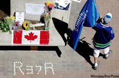 A fan carries a Vancouver Canucks flag at a makeshift memorial for former Canucks hockey player Rick Rypien outside Rogers Arena in Vancouver on Tuesday.